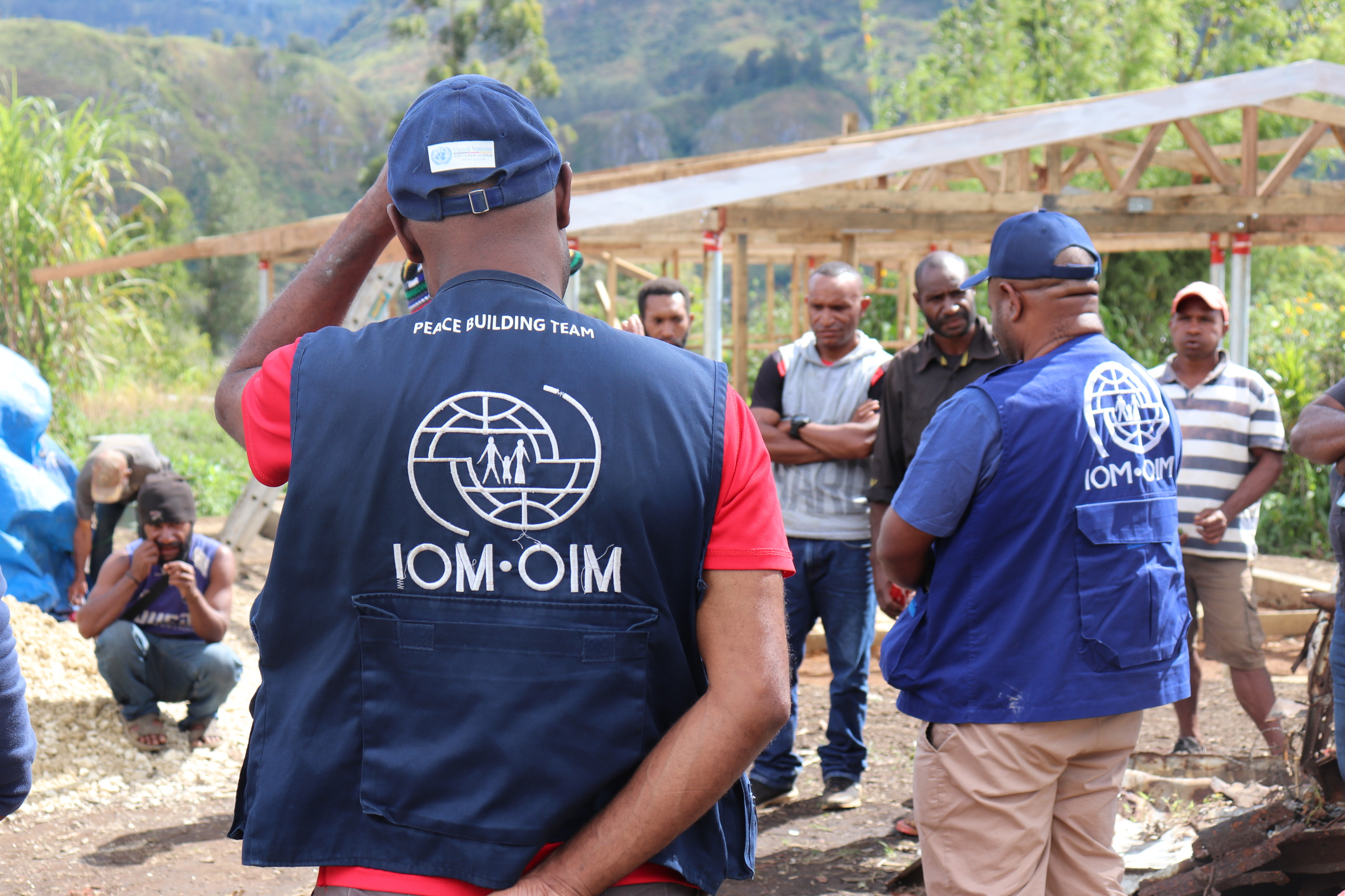 Man in IOM vest speaking with community members.