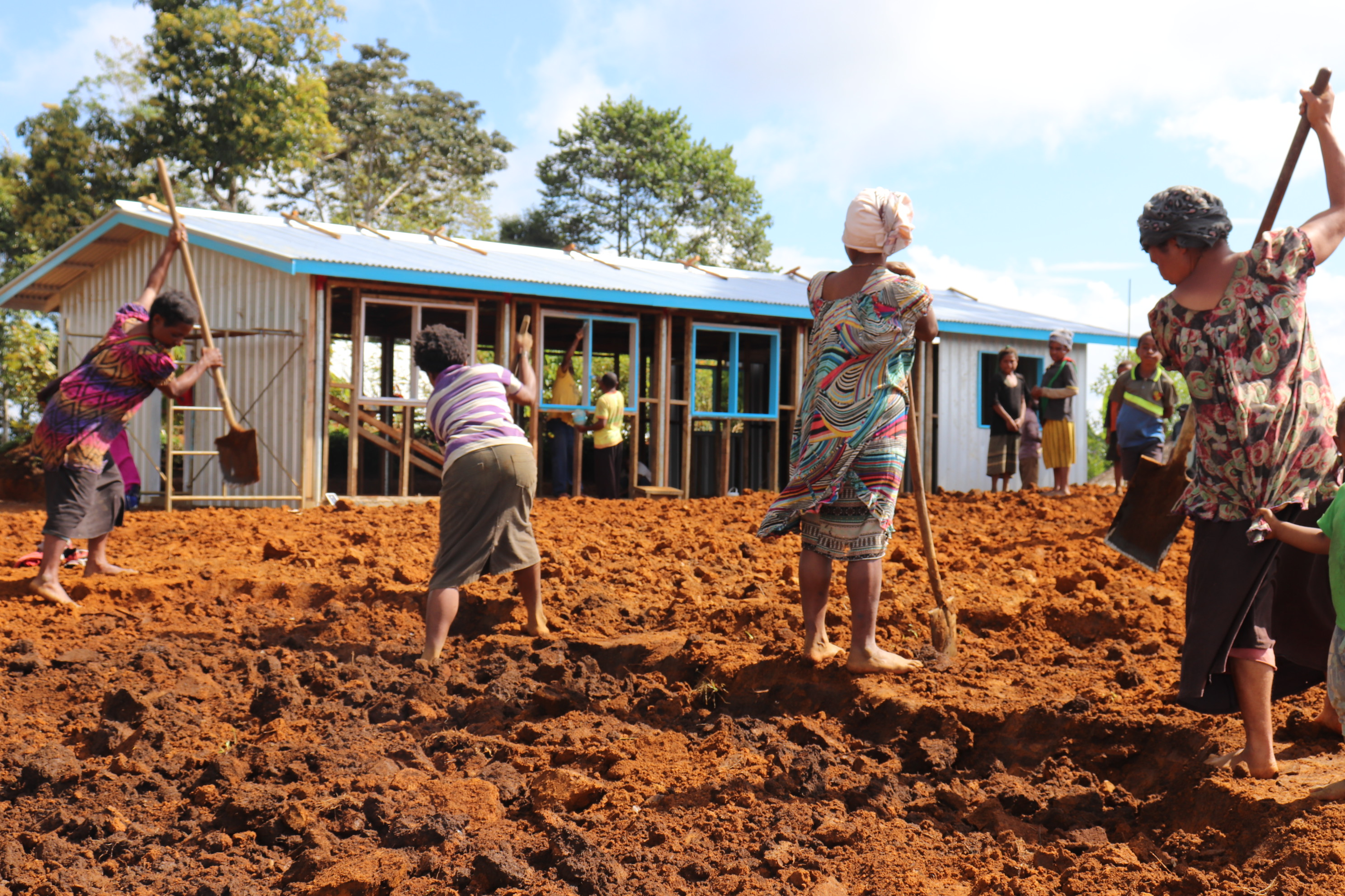 Women digging in field to prepare for building construction.