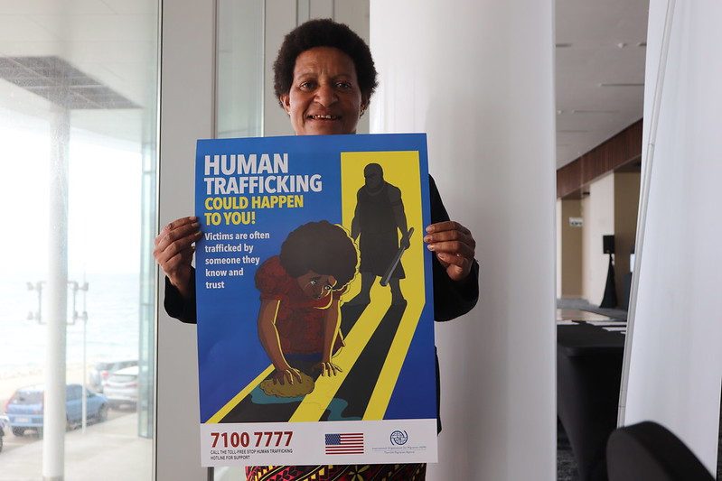 Woman holds poster on human trafficking