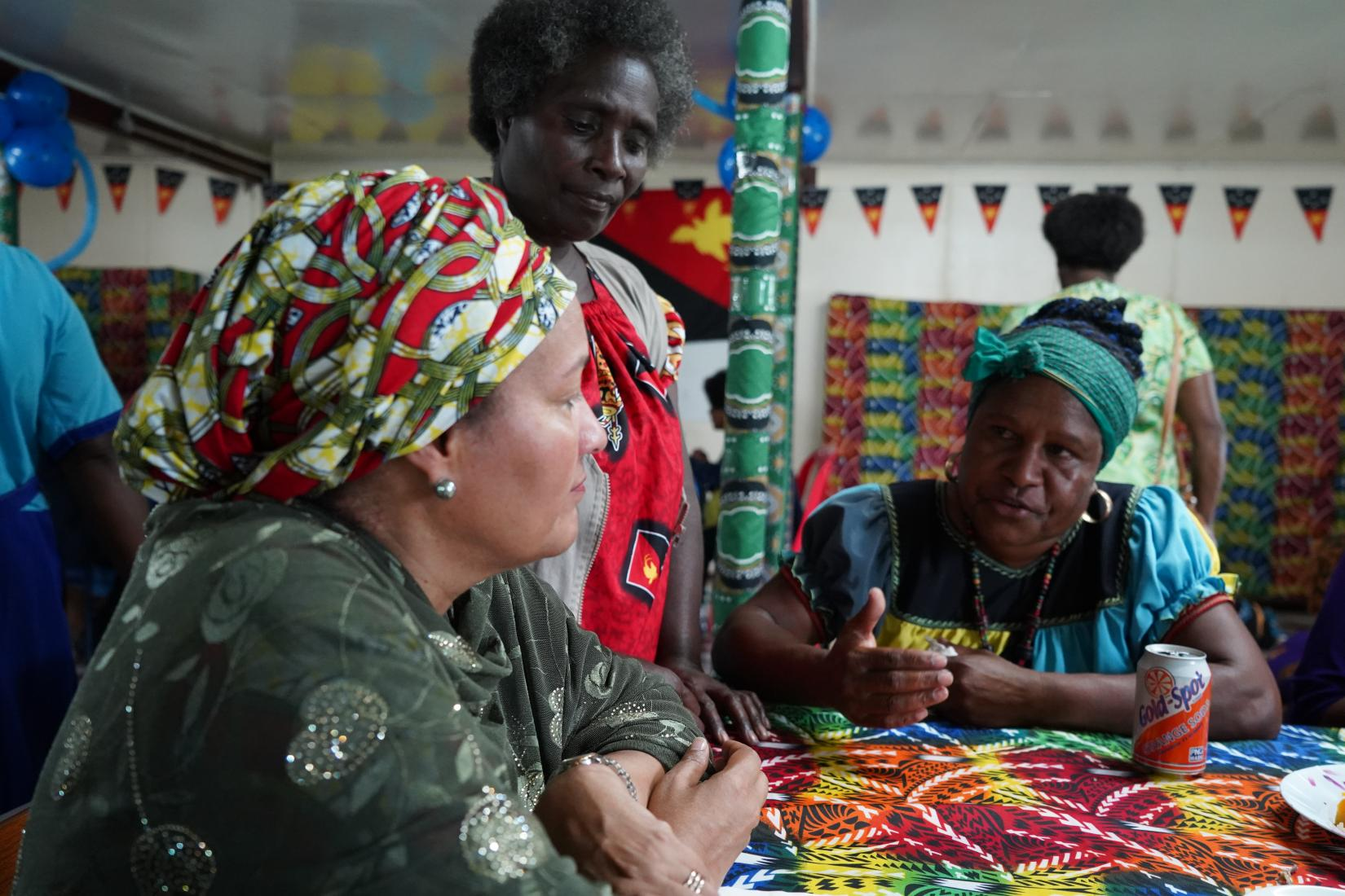 Amina Mohammed sites with local Hela woman.